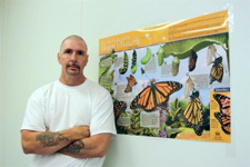 Washington State Penitentiary inmate Gilbert London stands next to a poster detailing the life cycle of a Monarch butterfly. London is one of six inmates helping to raise Monarch butterflies for WSU entomologist David James. Photo by Nella Letizia.