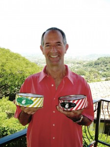 Robert Russell, a 1976 WSU alumnus who now lives in Costa Rica, displays unopened cans of Cougar Gold (left) and WSU American Cheddar. Russellbegan buying cans of cheeses manufactured by the WSU Creamery in 1972 when he started school.His three cans of Cougar Gold, made in 1973, are believed to be the oldest unopened cans of the WSU signature cheese. The American Cheddar was made in 1972