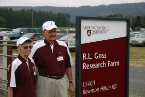 Marcie and Roy Goss admire the sign they have just unveiled at the entry to WSU's newly named R.L. Goss Research Farm in Puyallup.
