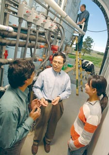 Biosystems engineer Shulin Chin and colleagues discuss the anaerobic digestor behind them.