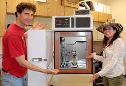 "John Ferguson and Melba Salazar-Gutierrez stand next to the ""vending machine."" Ferguson created the automated freezer sampler by modifying a standard environmental chamber to include a built-in slot at the bottom of the door, which earned the machine its nickname. Photo by Jakarat Anothai/WSU."