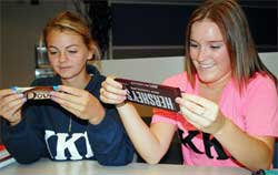 Students Kelsey Clifton and Samantha Young read the ingredients in a chocolate bar during a UCORE 201 class. Photo by Linda Weiford, WSU News.