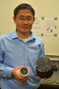 Haifang Wen in his laboratory holding a small can of cooking oil-based bioasphalt and a sample of the final hot mix asphalt (HMA).