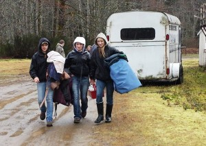 Snohomish County 4-H Youth Horse Program members Natasha Davis, Haley Fryrear, and Lilianna Andrews unload blankets and supplies for horses housed at the Darrington Rodeo Grounds. (Photo by Roxanne Nickerson).