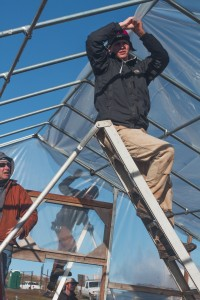 A volunteer holds the roof as it reaches the apex of the hoophouse frame.
