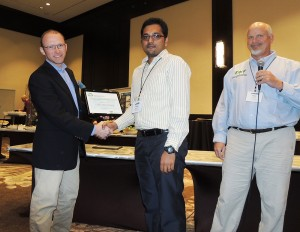 Thomas Bass, left, chair of the judging panel, and Mark Risse, right, congratulate George Neerackal on his poster win at Waste to Worth. (Courtesy photo)