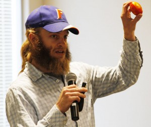 """Spencer Marshall, a graduate student in Plant Pathology, holds up an imported grocery-store tomato infected with spotted wilt virus during his presentation at the """"Science at IAREC"""" expo."""