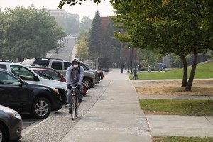 A mask-wearing cyclist moves alongside a hazy WIlson Road Wednesday afternoon, Aug. 26, in Pullman.