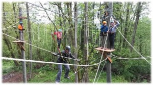 A group navigates the various ropes challenges on the course at Camp Long.