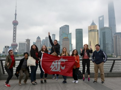 Students show their Coug flag on Shanghai's famous Bund waterfront, with views of Pudong's skyscrapers. From left are Yeseily Pruneda, Tatiana Sweat, Nikki‎ Norman, Ariana Paynter, Katie Rae, Alison DePhillips, Graciela Vela, Kaitlyn Jo Engle, and Assistant Professor Ting Chi.