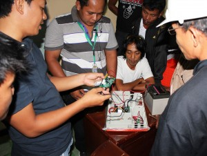 Elmar Villota, left, educates Filipino residents on basic maintenance and troubleshooting for an energy device.