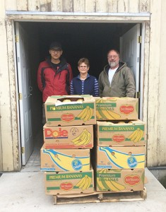Heng Cai, organic major and student farmer, delivers a load of winter squash to Colfax food pantry volunteers  Gail McNeilly and Dean Hall.