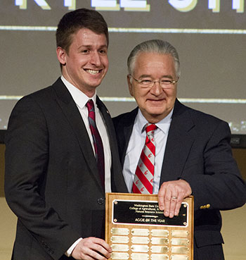 Kyle Strachila receives his 2017 Aggie of the Year award from Dean Ron Mittelhammer.