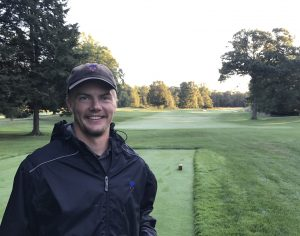 Harke poses for a portrait photo on a golf course.