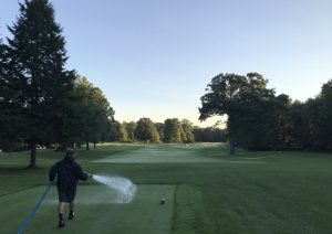 Harke drags a hose and sprays water on a golf course.