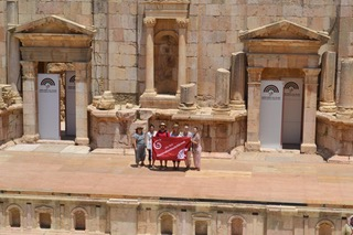 SDC students display a Cougar flag in a stop at the South Theater in Jerash, Jordan.