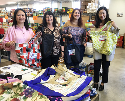 Three faculty members and a staffer show off colorful shopping bags at the food bank.