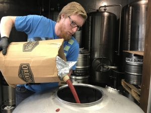 Caleb Wiebe pours a pink liquid into a giant stainless steel vat.
