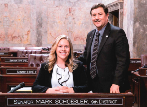 Foote sitting at the desk of Senator Schoesler, with Schoesler standing next to her