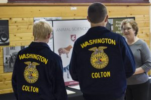 Two FFA students talk with a woman in front of a sign for the Department of Animal Sciences at WSU.