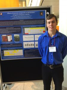 Brennan stands in front of his research poster, hanging from a board.