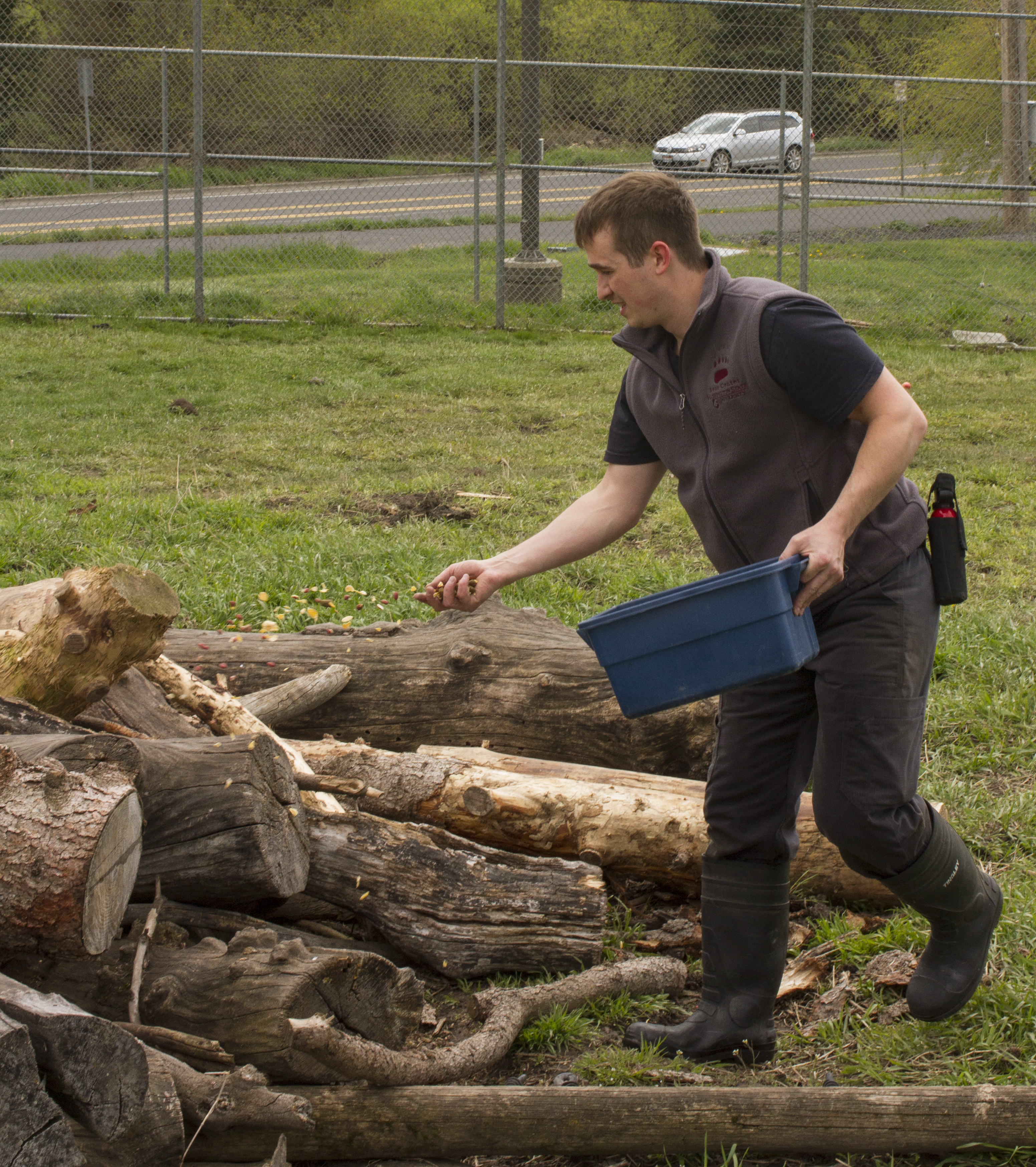 Brandon holds a bucket in one hand and throws food onto a pile of wood with the other hand.