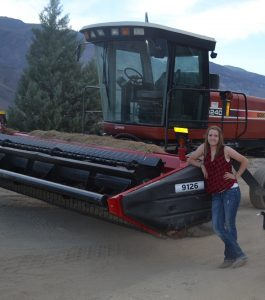 Katie Doonan leans on a farming combine in a field.