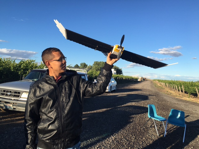 Precision-ag researcher Manoj Karkee holds up a flying drone in a vineyard.