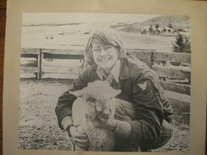 An old black and white photo of Mike Hacket crouched down with his arms around a sheep.