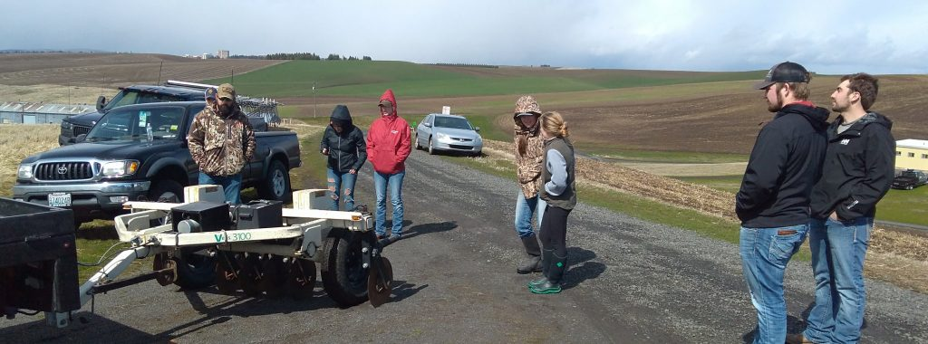 WSU students deploy a soil-mapping cart at a research field.