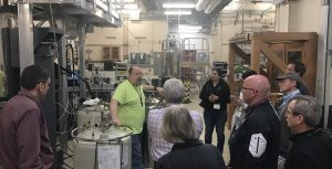 Tour members look at equipment and hear a tour guide speak at Pacific Northwest National Laboratory.