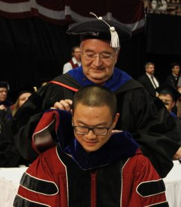 Ron Mittelhammer presents a hood to new School of Economic Sciences graduate Xiangrui Wang during 2018 commencement.