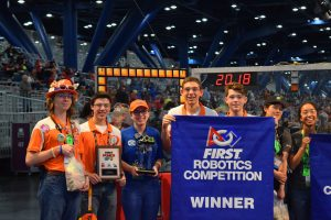 five high school kids hold up a banner that says FIRST Robotics Competition WINNER and a plaque.