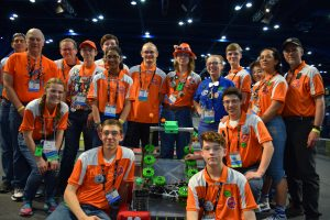 Group photo of robot team designers, all wearing bright orange team shirts, pose around their robot. the robot is short and rectangular with around a dozen neon green wheels.