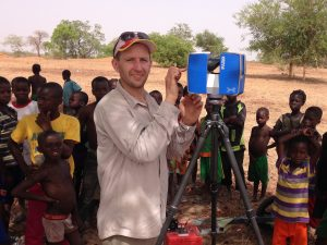 Alex Fremier posing with a special camera in a desert, surrounded by African children.