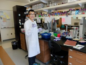 Xiaochi Ma stands in front of a messy lab bench, covered with papers, vials, and machinery.