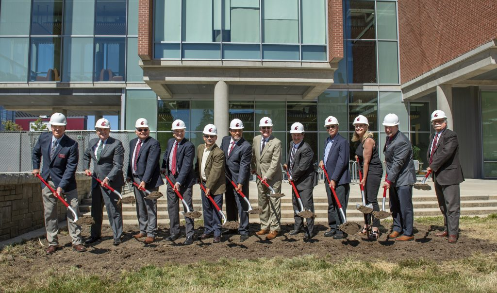 Dignitaries ceremonially break ground, lifting dirt with shovels at the future site of the Plant Sciences Building.