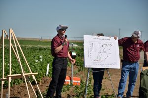 Speakers in front of a chart and easel at the Othello field day, with potato plants in the background.