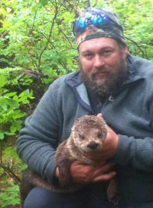 Tony Carnahan holds a river otter in two hands in a forest setting,