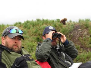 Two men look toward the camera, one with binoculars at his eyes, as they sit outside. A grizzly bear is in the distance behind them.