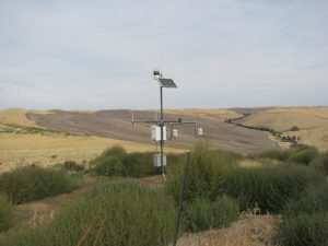Automated weather station among low weeds, with brown hills in background.