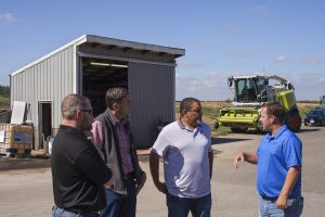 Four men talk in front of building with a green combine in the background.