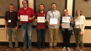 Group photo of WSU participants in the June competition, holding pieces of paper.