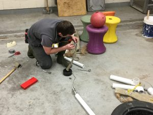 Brandon crouches on a concrete floor surrounded by PVC pipe, pulleys, wrenches and sockets, a tire, and large, colorful plastic spindles.