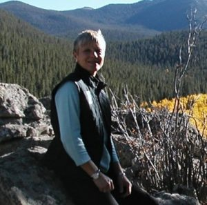 Nancy Irlbeck sits on a rock with forest covered mountains in the background.