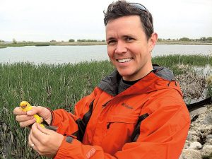 Owen holds a yellow piece of plastic and wears an orange jacket with a pond on the background.