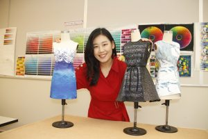 Chanmi Hwang holds several colorful dress forms in front of a wall of printed digital color templates.