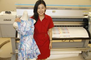 Hwang with a dress-displaying mannequin, next to a large printing machine.