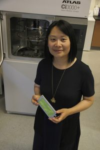 Holding a strip of green cloth, Hang Liu demonstrates use of a large piece of advanced lab equipment.