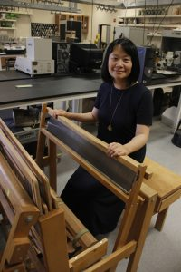 Hang Liu sits at the controls of an wooden, hand-worked loom.